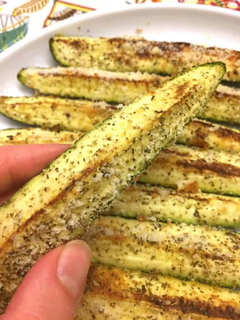 Fingers holding one Baked Parmesan-Garlic Zucchini spear above a plate of seven more.
