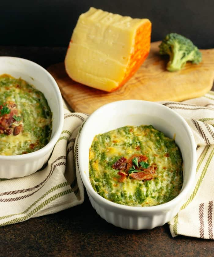 Two white bowls of Cheesy Broccoli Mash with Bacon and a wedge of cheese in the background.