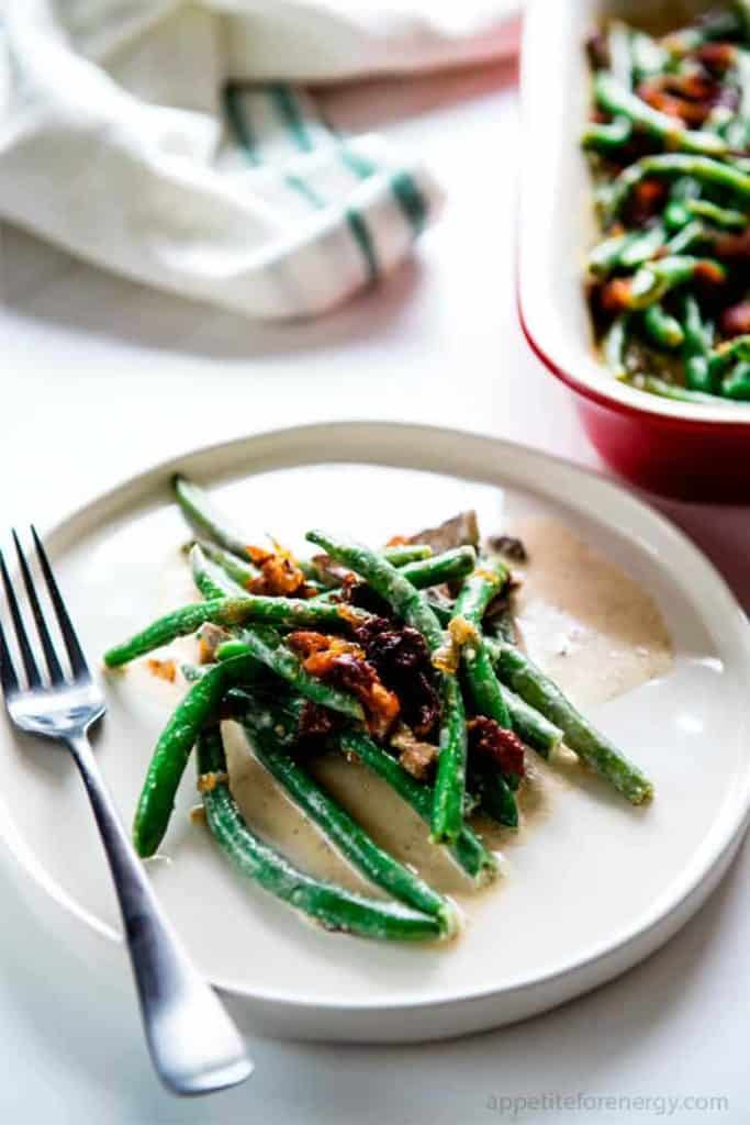 Sauteed Green Beans in Bacon Cream Sauce on a small white plate with a fork.