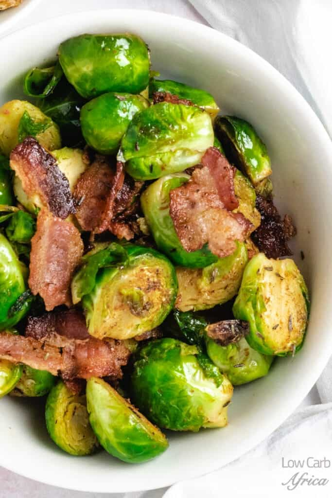 Closeup of Stir Fried Brussels Sprouts with Bacon in a white bowl.
