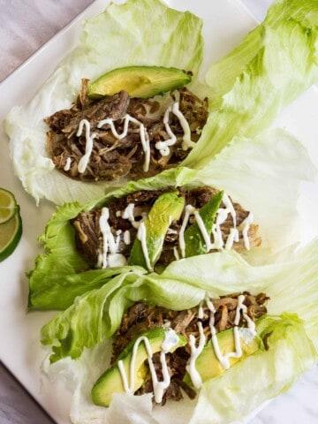 three lettuce wrapped al pastor pork carnitas on a plate