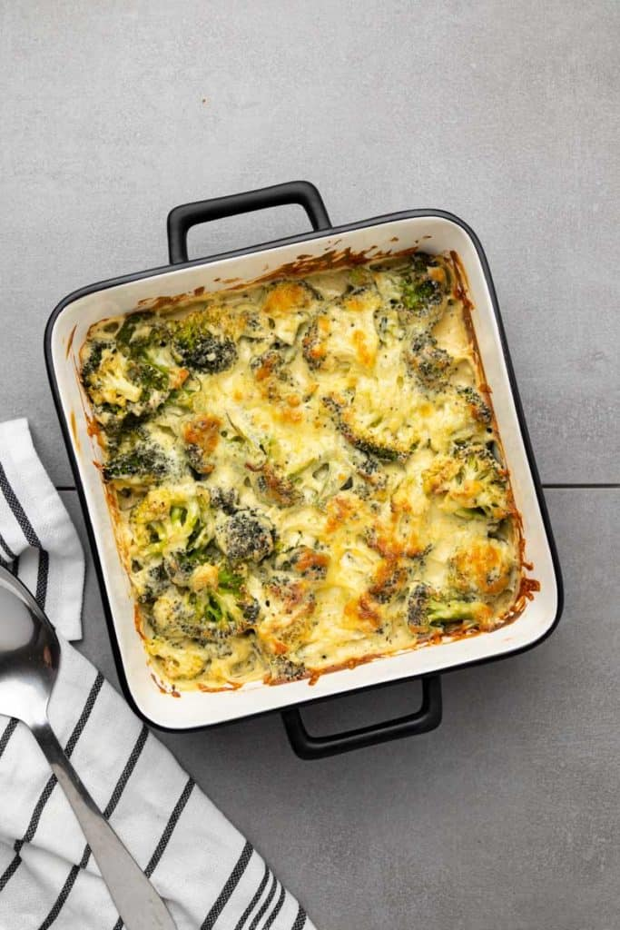 Keto Broccoli Casserole in a square baking dish next to a serving spoon.