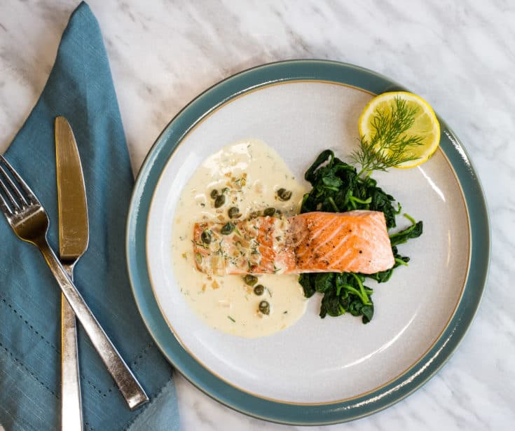 keto salmon with lemon dill cream sauce on a plate with sauteed spinach