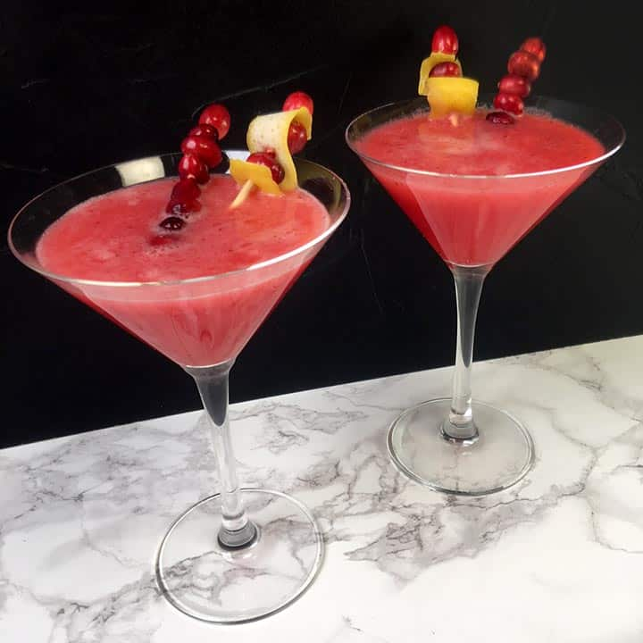 Two cranberry lemon drop cocktails in martini glasses with fruit garnish.