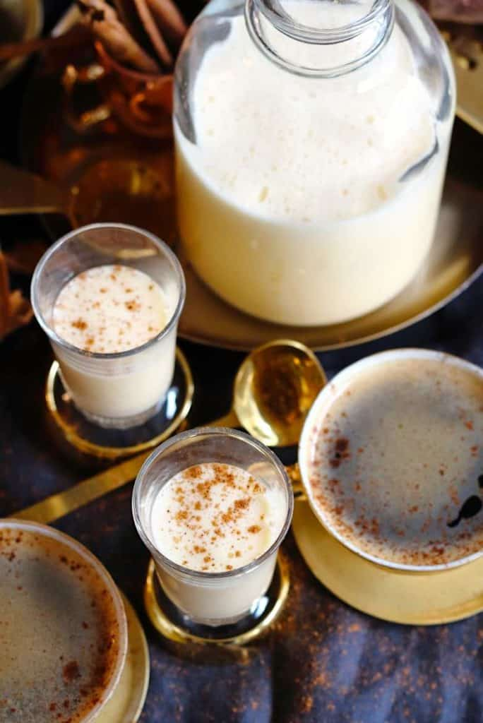 Two glasses of egg nog and two cups of egg nog coffee with a pitcher of egg nog in the background.