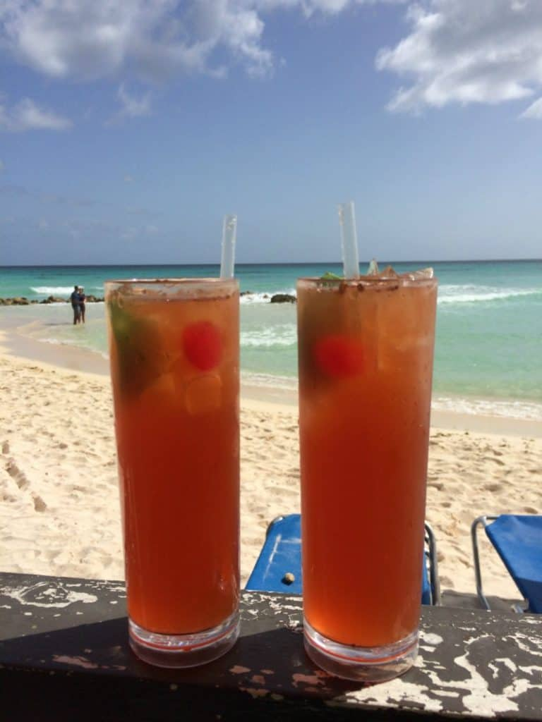 Two Barbados Rum Punch glasses with ice and straws on a beach in front of the water.