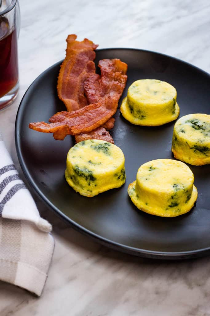 Four Keto Egg Bites with Spinach and Cheese on a black plate with bacon.