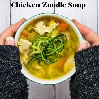 keto chicken zoodle soup in a bowl held between two hands