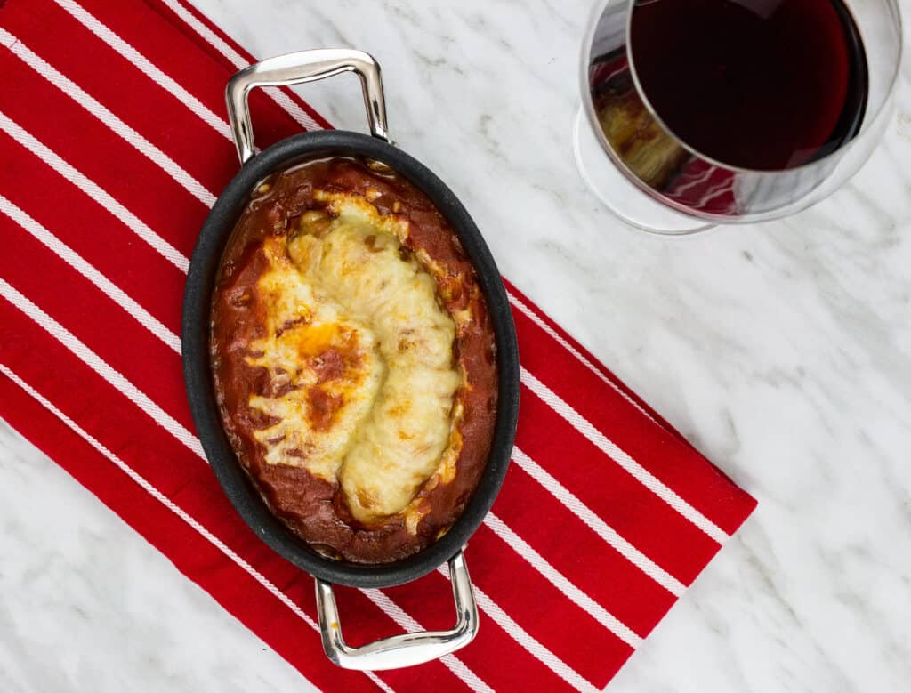 sausage parmigiana in a serving dish and a glass of wine
