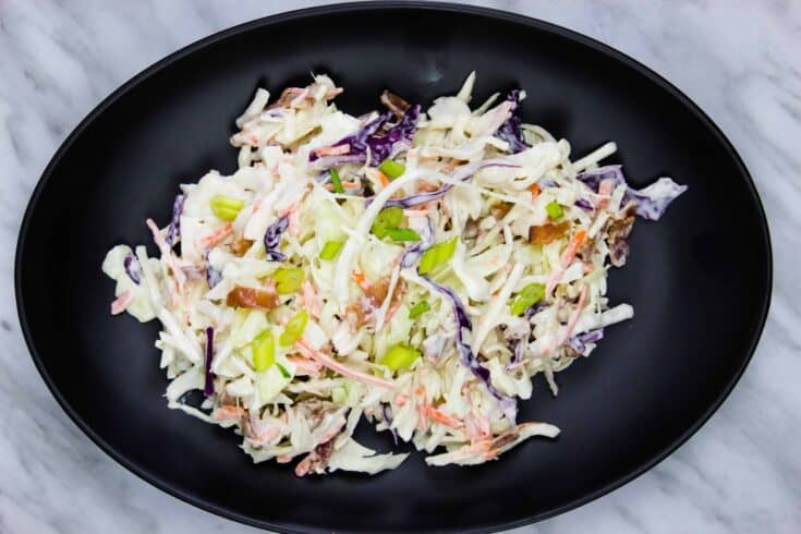 pickle slaw with bacon on a black oval plate