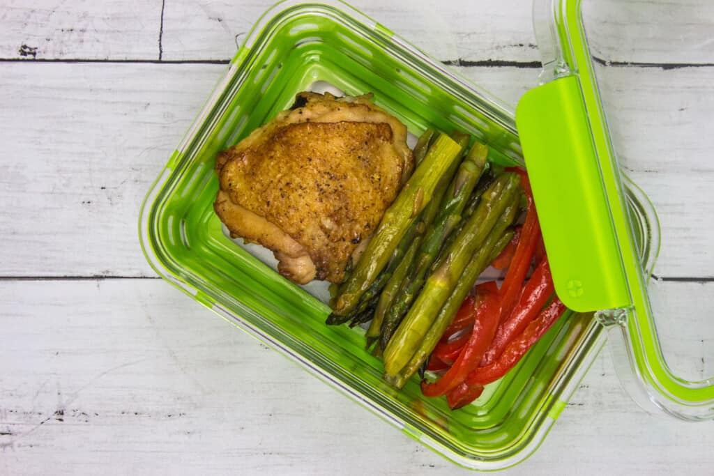 Garlic chicken skillet with asparagus and red bell pepper in a meal prep conatainer