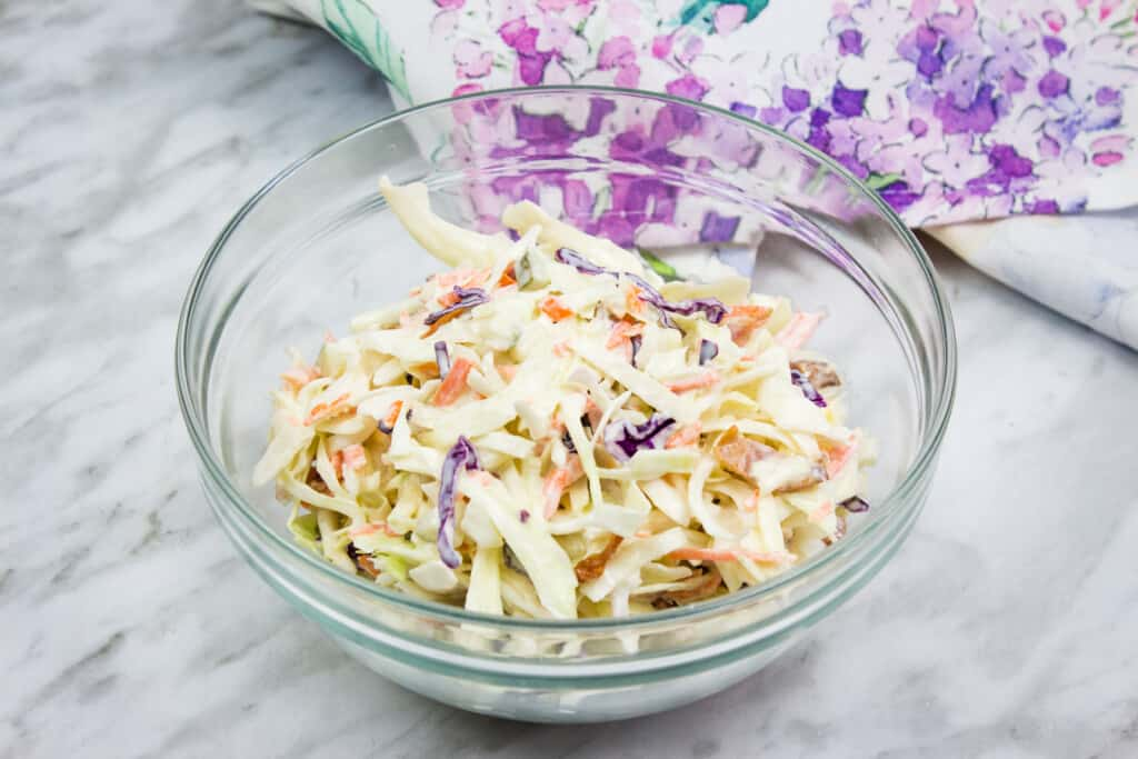 pickle slaw with bacon in a glass bowl