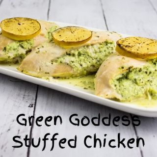 Three chicken breasts, baked with a filling of Green Goddess herbed cream cheese mixture and a slice of lemon on top, resting on a white plate.