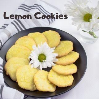 keto lemon cookies on a black plate with a daisy in the middle and in the background