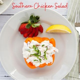 southern chicken salad in an orange bell pepper cup with a strawberry and lemon wedge on the side