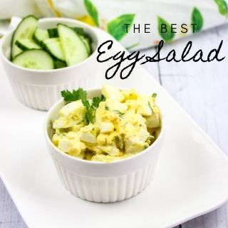 the best egg salad in a ramekin with cucumber slices in the background