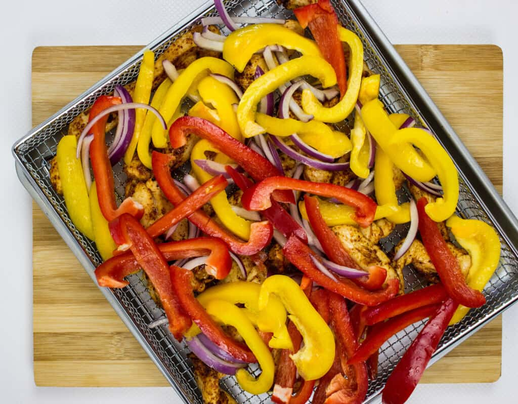 add cut onions and peppers to the top of the chicken and air fry a few more minutes