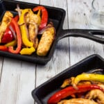 two portions of air fryer fajitas on square cast iron plates