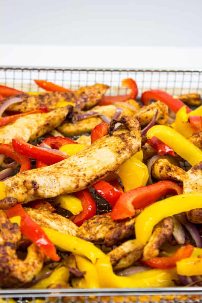 air fryer chicken with peppers and onions in the air fryer basket ready to eat
