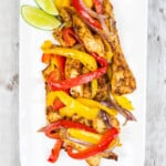 air fryer fajitas on a long white plate with lime wedges