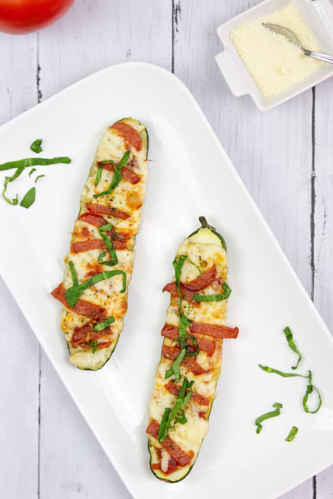 Two zucchini pizza boats on a plate