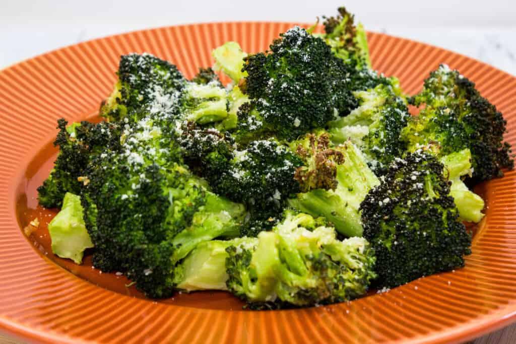 keto broccoli with parmesan and garlic on an orange plate