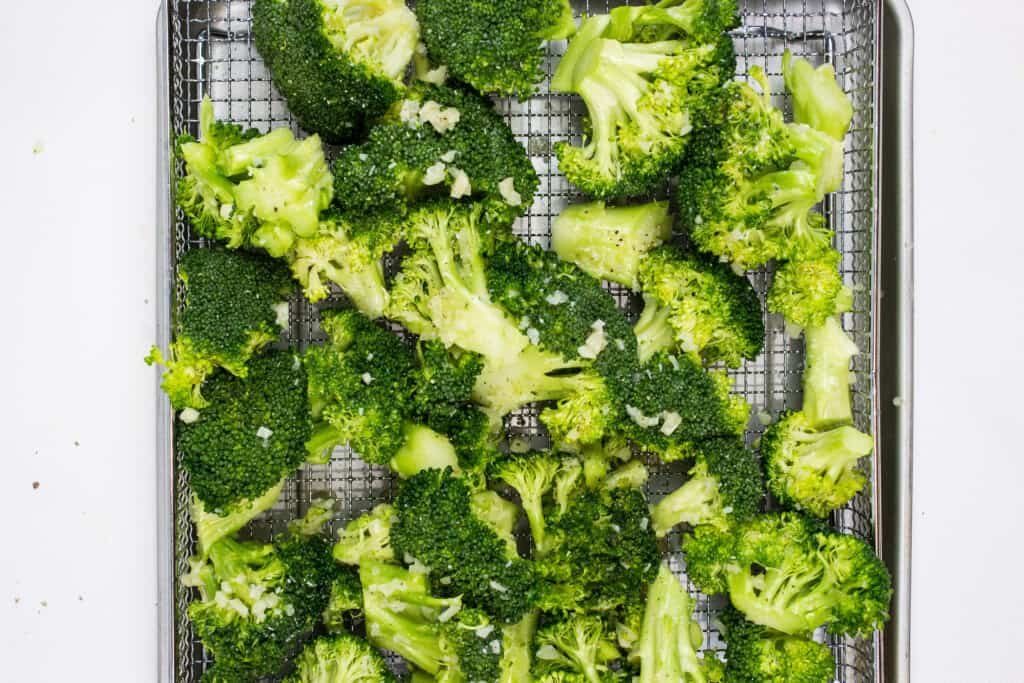 load the seasoned broccoli into an air fryer basket and cook