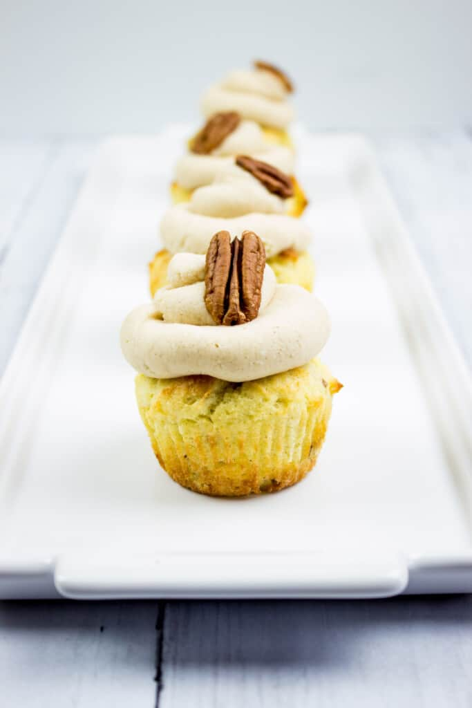 pecan cupcakes with brown butter cream cheese icing on a plate