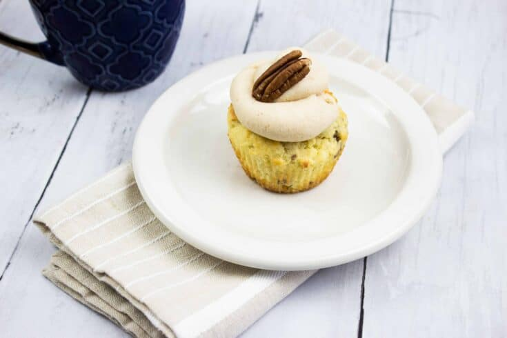 keto pecan cupcake with brown butter cream cheese icing on a plate, coffee cup in background