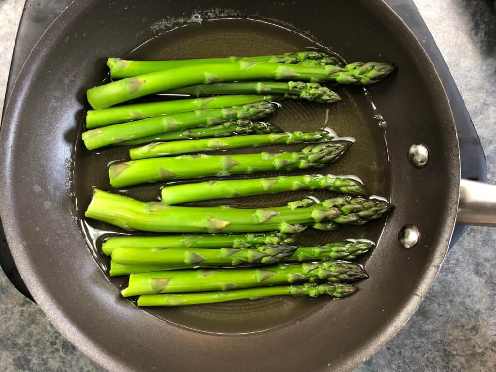 asparagus in a skillet with a wee bit of water