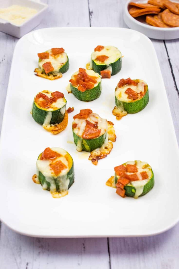 zucchini pizza bites on a rectangular white platter