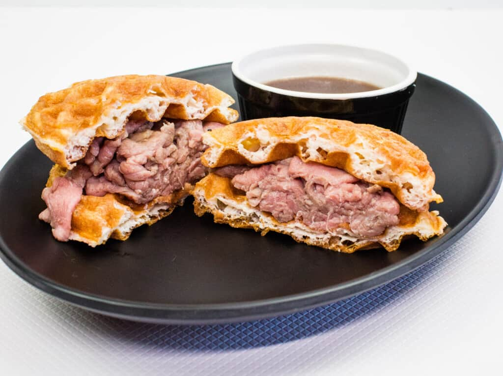 keto french dip chaffle sandwich cut in half on a black plate with a side of au jus