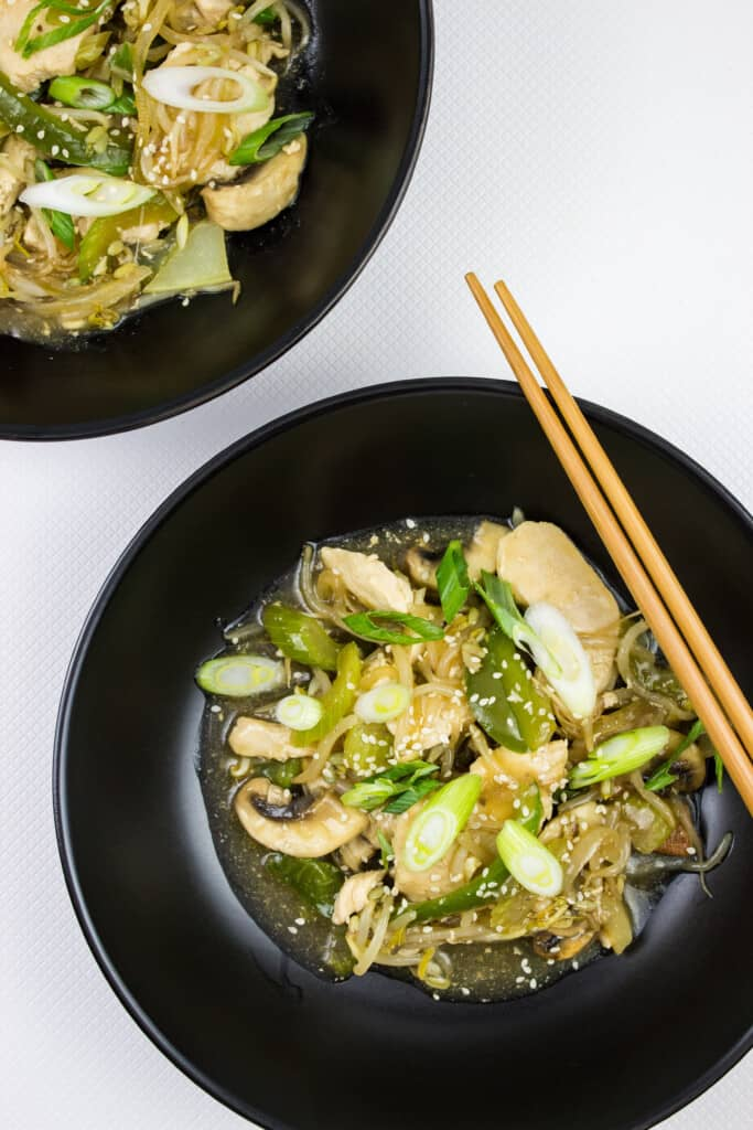 keto chicken stir fry in two black bowls with chopsticks