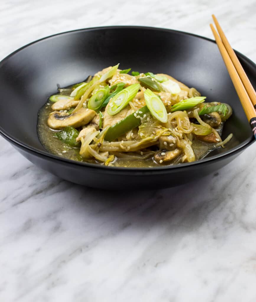 keto chicken stir fry in a black bowl with chopsticks on the side
