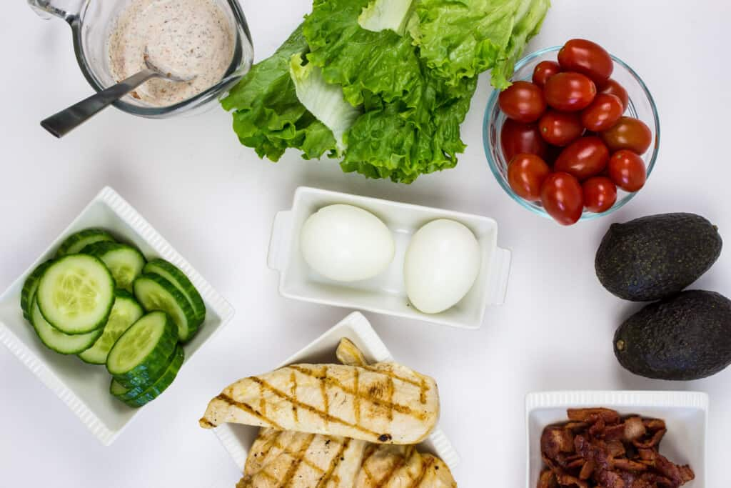 ingredients to make keto cobb salad (chicken, egg, tomatoes, lettuce, avocado, bacon, cucumbers, dressing)