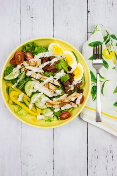 keto cobb salad with a drizzle of ranch dressing on a yellow plate