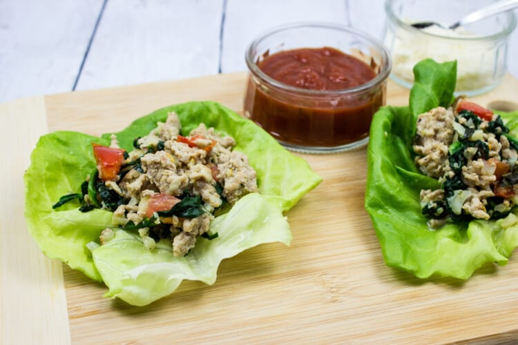 italian style keto ground chicken wraps on a board with sauce