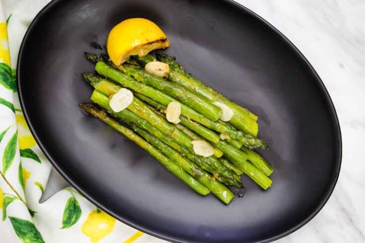 keto pan roasted asparagus with lemon on a black plate