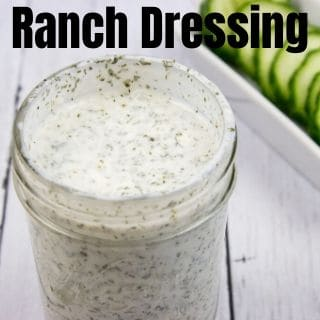 ranch dressing in a jar with cucumbers in background