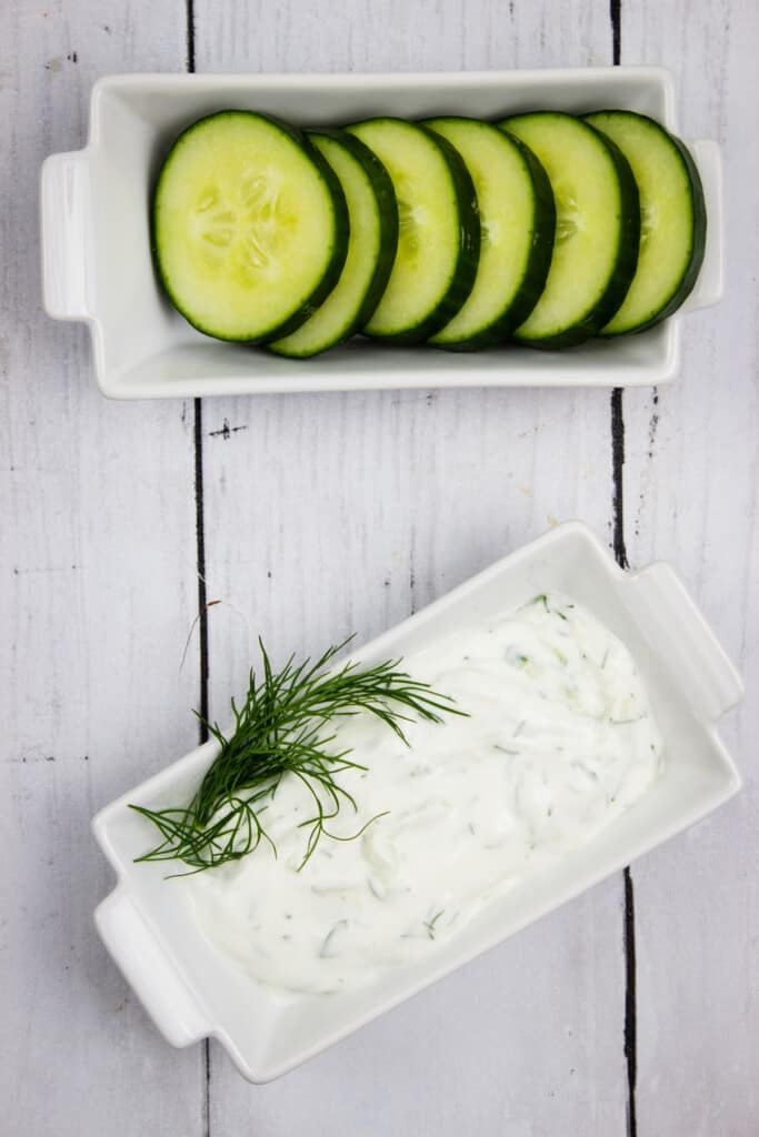 tzatziki sauce keto in a dish with sliced cucumbers on the side