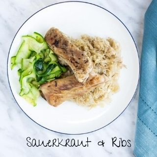 ribs and sauerkraut on a round plate with zucchini ribbons