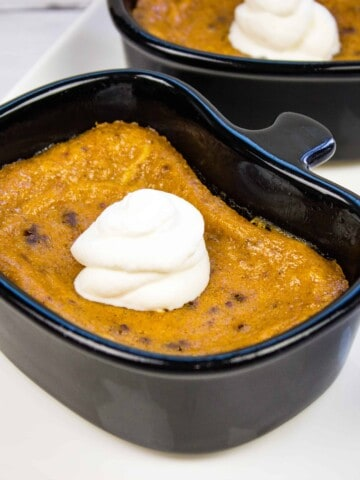 keto pumpkin custard in a black ramekin with a dollop of whipped cream