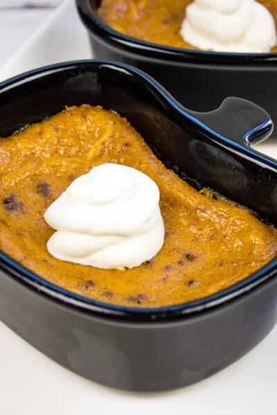 keto pumpkin custard in a black ramekin with a dollop of whipped cream