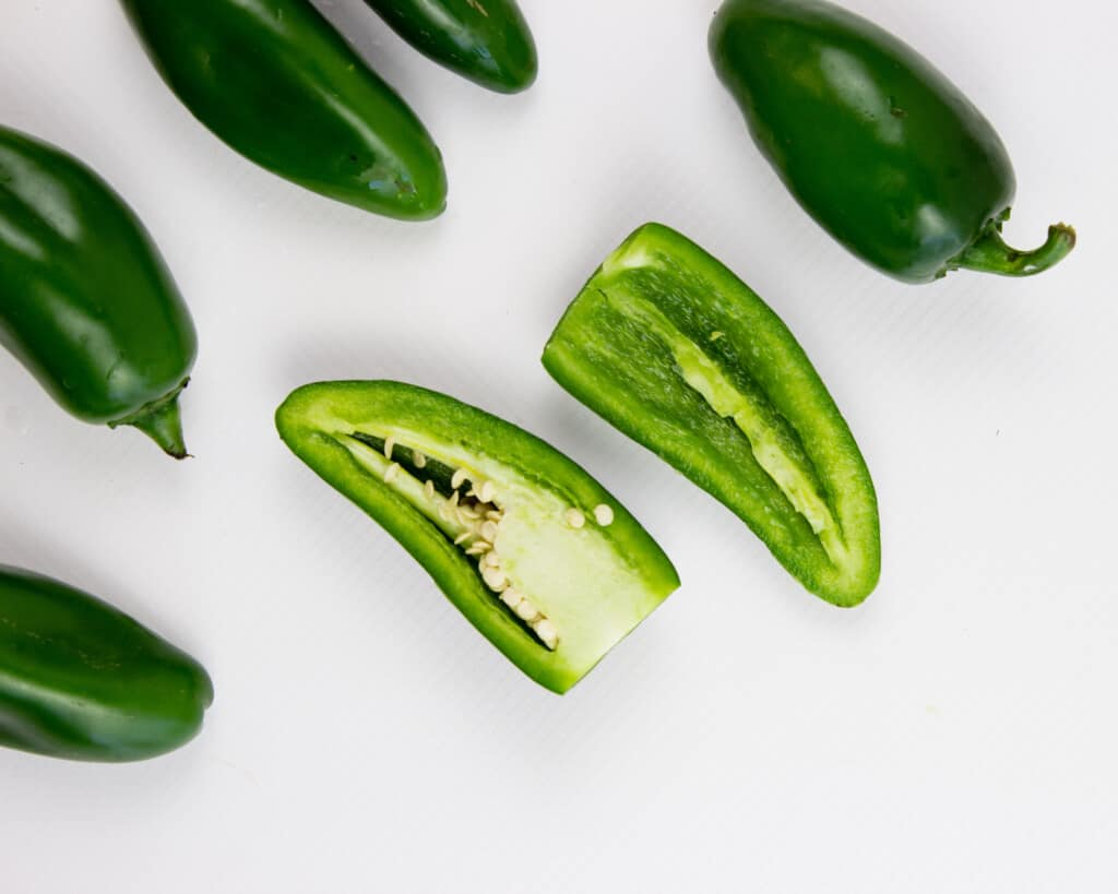 cut jalapenos in half with sharp knife