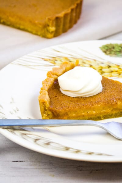 keto pumpkin pie on a plate with whipped cream