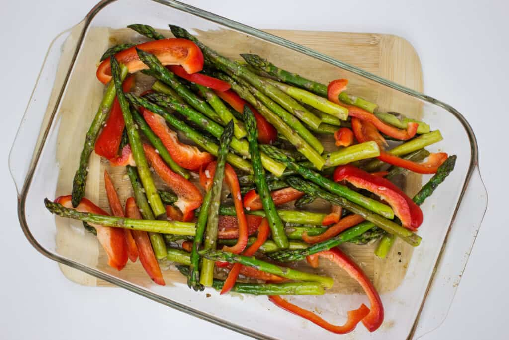 adding peppers to the roasted asparagus