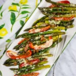 keto cheesy baked asparagus with bacon and peppers on a white serving platter