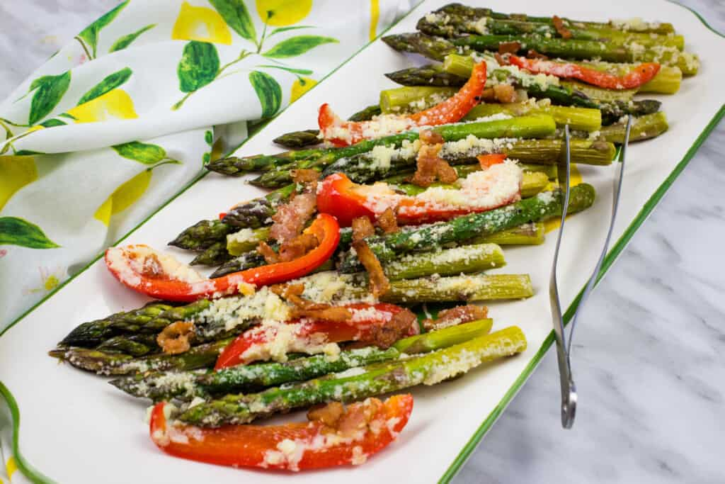 keto cheesy baked asparagus with bacon and bell peppers on a platter