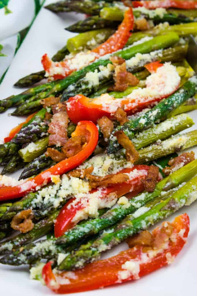 a closeup of keto cheesy baked asparagus with red peppers and bacon