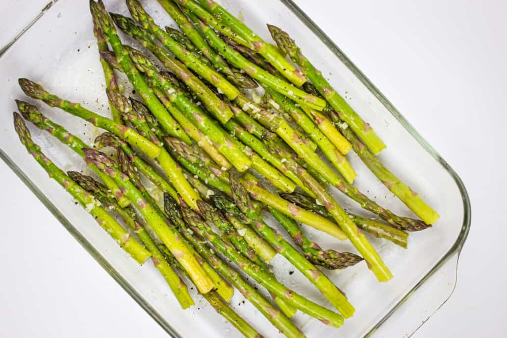 roasted asparagus in a baking dish before adding cheese and bacon